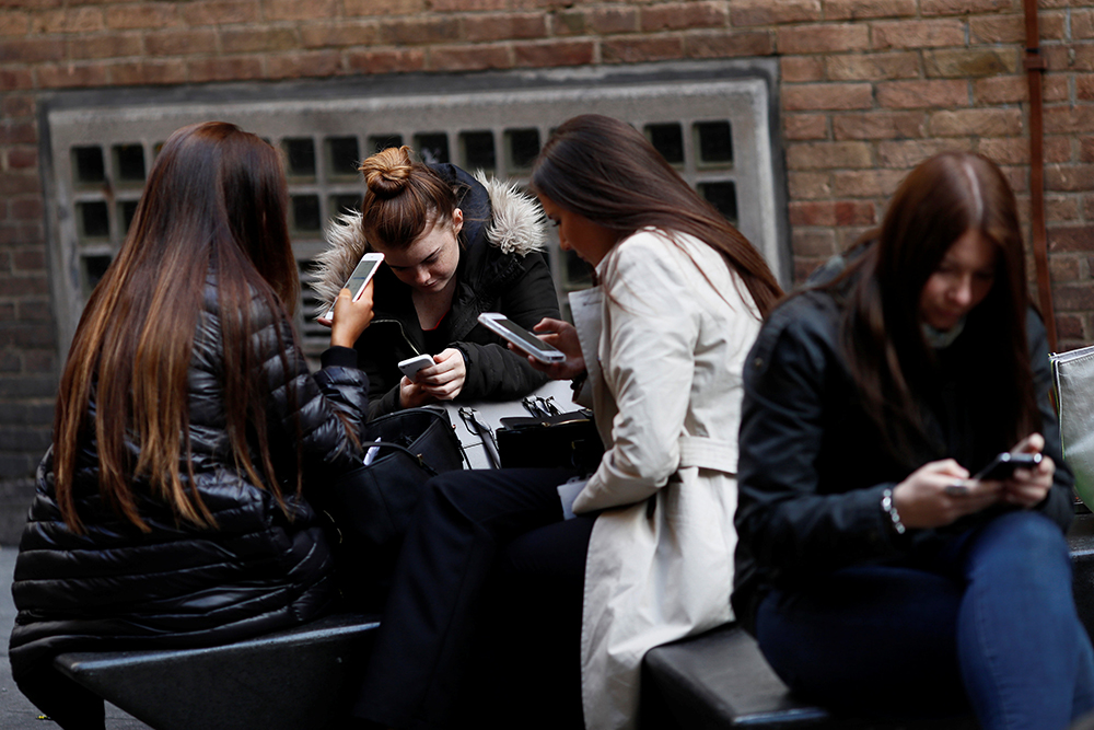 """Women look at their mobile phones in London, Britain October 6, 2016. REUTERS/Stefan Wermuth  SEARCH """"WERMUTH PHONES"""" FOR THIS STORY. SEARCH """"THE WIDER IMAGE"""" FOR ALL STORIES."""