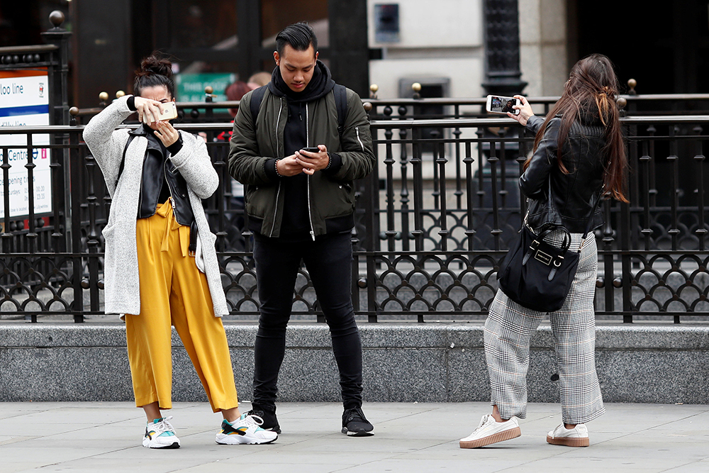 """People look at their mobile phones at Piccadilly Circus in London, Britain October 6, 2016. REUTERS/Stefan Wermuth  SEARCH """"WERMUTH PHONES"""" FOR THIS STORY. SEARCH """"THE WIDER IMAGE"""" FOR ALL STORIES.?"""